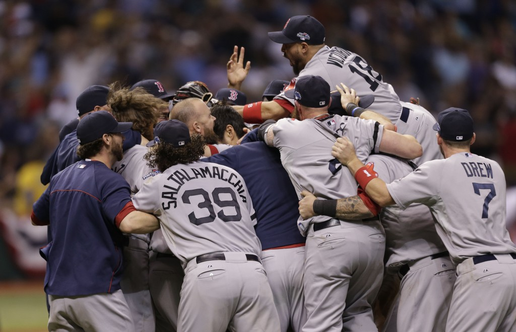 The Boston Red Sox's celebrate on the field after defeating the Tampa Bay Rays in Game 4 of an American League baseball division series, Wednesday, Oct. 9, 2013, in St. Petersburg, Fla. The Boston Red Sox's defeated the Tampa Bay Rays 3-1 to move on to the American League Championship Series.