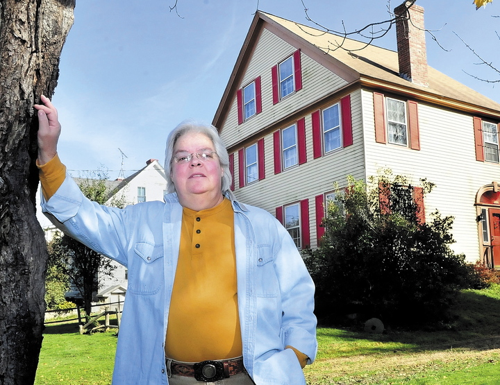 "Marty Golias, originally from Salem, Mass., stands in front of her home on the Falls Road in Benton where she has lived for 13 years. She believes that the house, which is described as haunted in Tom Verde's book ""Maine Ghosts and Legends,"" is home to friendly spirits."