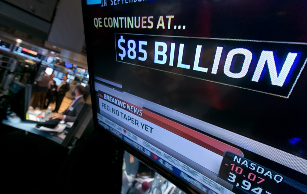 The decision of the Federal Reserve appears on a television screen on the floor of the New York Stock Exchange on Wednesday. The Fed said in a statement after a two-day policy meeting that it will keep buying $85 billion a month in bonds to keep long-term interest rates low and encourage more borrowing and spending.