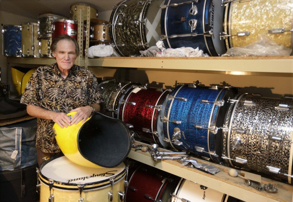 James Glay poses with his collection of vintage drums in Arlington Heights, Ill. When he was laid off from his sales job he joined a growing number of older people and created his own.