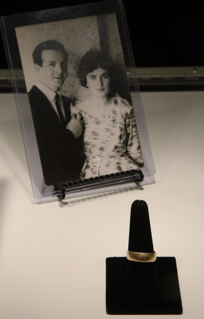 Lee Harvey Oswald's wedding ring is displayed in front of a photo of Lee Harvey Oswald and his wife, Marina Oswald.