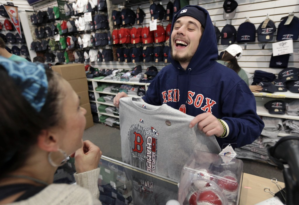 Worker Jake Miskin laughs with Lori Leduc of Calgary, Alberta, Canada as she buys a 2013 World Series champions shirt at a shop near Fenway Park in Boston on Thursday.
