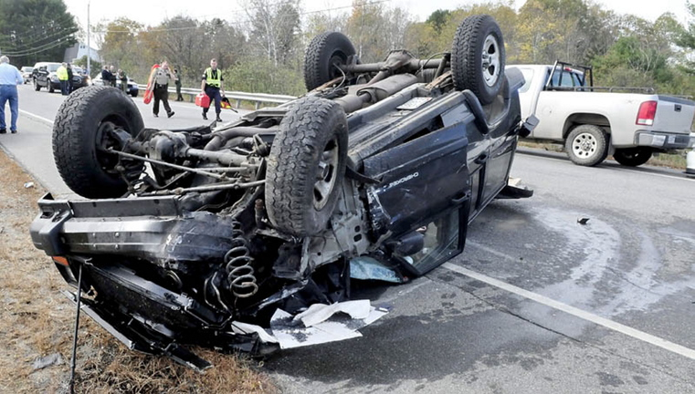 A Jeep Cherokee lies upside down where it landed after plowing into a vehicle on the side of Route 150 in Skowhegan on Thursday. Police said the father and son who were riding in it were not injured in the crash, which involved four vehicles, including two Maine Warden Service trucks. A state game warden, one of two at the scene, suffered minor injuries, police say.