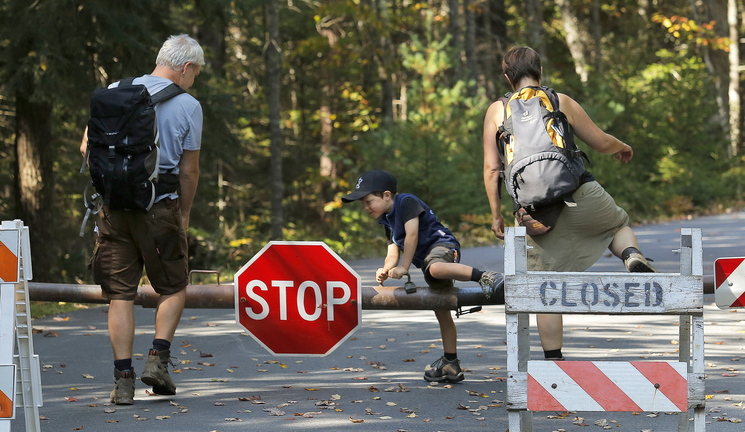 Despite the closed sign, Titus Steinberg, 5, of Herne, Germany, hops over the gate at Acadia National Park's Echo Lake in Southwest Harbor on Wednesday, along with his parents Oliver, at left, and Ramona.