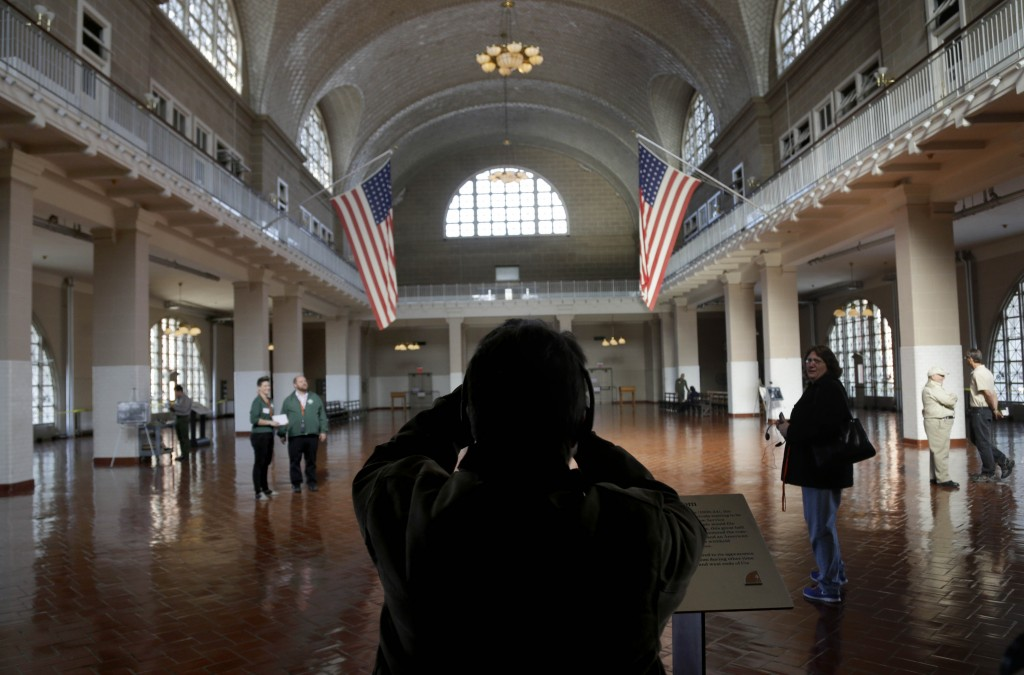 A visitor to the newly re-opened Ellis Island takes a picture of the registry room on Monday. The island that ushered millions of immigrants into the United States received visitors Monday for the first time since Superstorm Sandy flooded its basement.