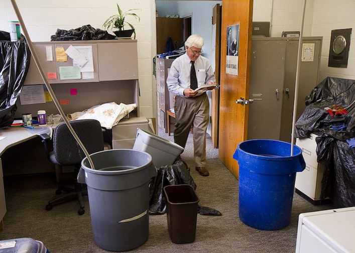 Rob Wood, director of Portland's Adult Education Program, reviews a document in his office near barrels set up to collect water in June from a leaking roof at the West School. Gov. Paul LePage's government efficiency agency is recommending a $9.5 million cut for public school districts in order to balance the state's budget.