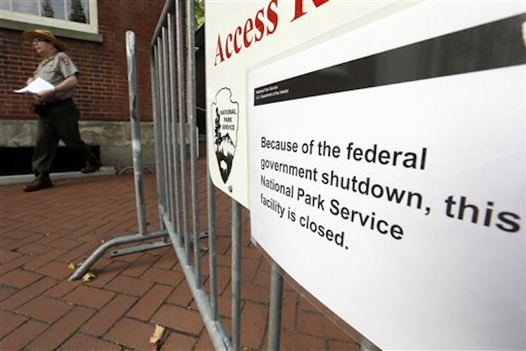 A National Park Service employee exits the courtyard of Independence Hall in view of a posted sign saying the facility is shut down at Independence National Historical Park on Tuesday in Philadelphia.