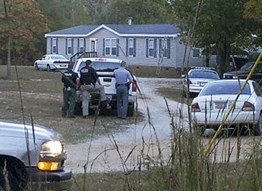 Law enforcement officials stand near a home on Callison Highway where six people were found dead on Tuesday in Greenwood, S.C.