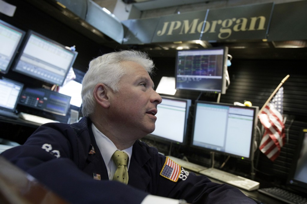 Peter Castelli, a vice president with JP Morgan, works in his firm's booth on the floor of the New York Stock Exchange.