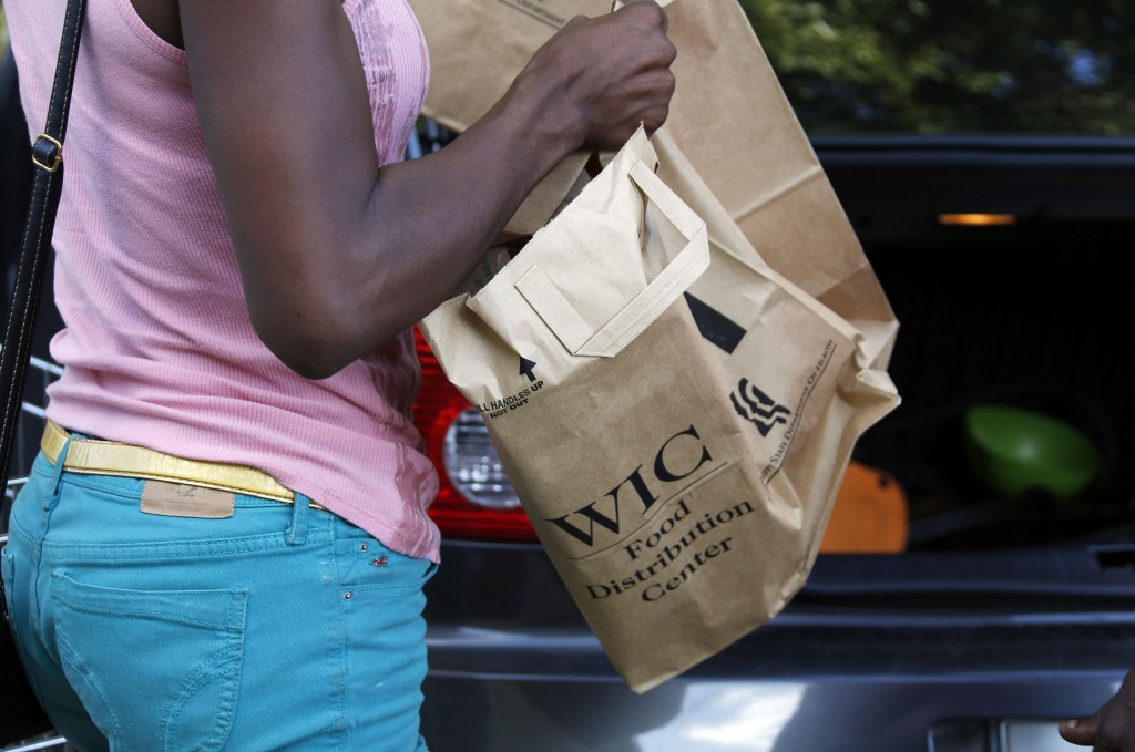 A recipient of the Special Supplemental Nutrition Program for Women, Infants and Children, better known as WIC, loads food into her car after leaving a center in Jackson, Miss., on Thursday. Despite a partial shutdown of the federal government, Mississippi has gotten permission to keep operating WIC through October. WIC helps pregnant, breastfeeding and post-partum women, plus infants and children younger than 5.