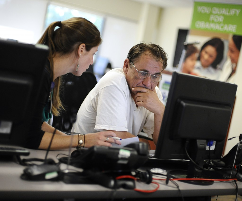 Shannon Bali helps Boguslaw Dudek enroll in the new health insurance system Tuesday at the Community Health Center in New Britain, Conn. Despite design recommendations, the federal website does not allow for window shopping.