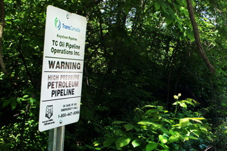 A sign for the Keystone tar sands pipeline stands by a bike path in Edwardsville, Ill., in 2010. The controversial South Portland Waterfront Protection Ordinance is aimed at forestalling the potential handling of tar sands in the city.