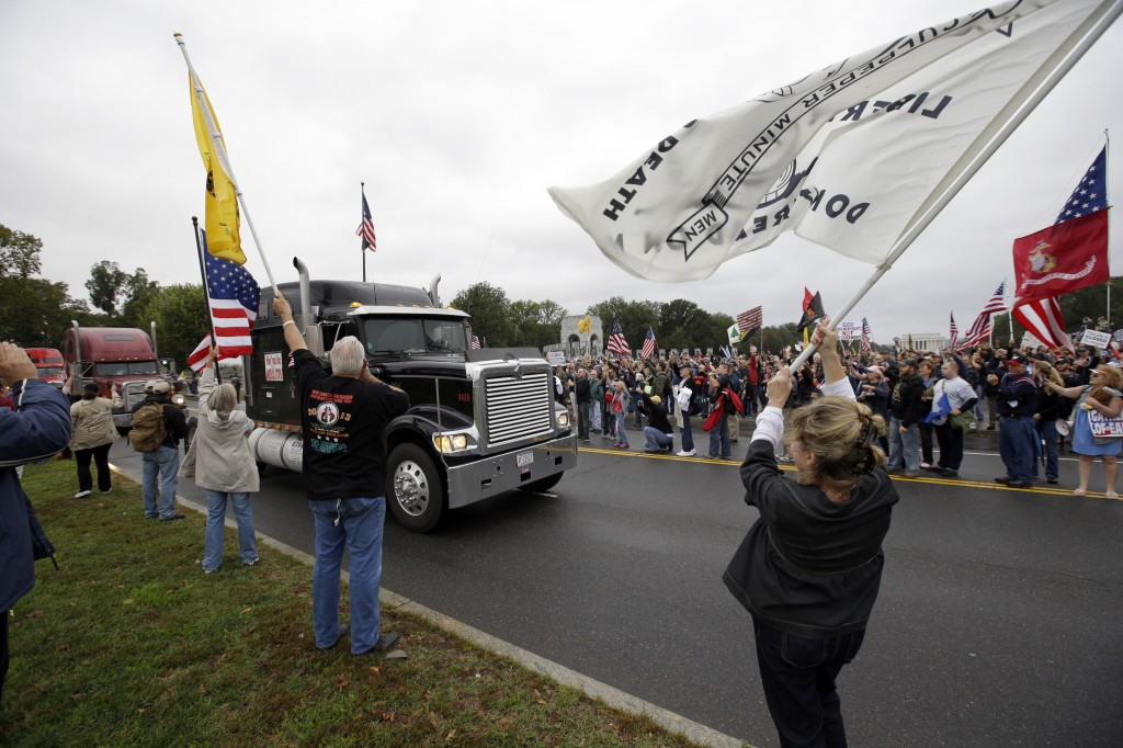 Protesters cheer as large trucks arrive at a rally at the World War II Memorial on the National Mall in Washington Sunday, Oct. 13, 2013. Leaders in the U.S. Senate have taken the helm in the search for a deal to end the partial government shutdown and avert a federal default. The rally was organized to protest the closure of the Memorial, subsequent to the shutdown, and lack of access to it by World War II veterans, who traveled there on Honor Flight visits.