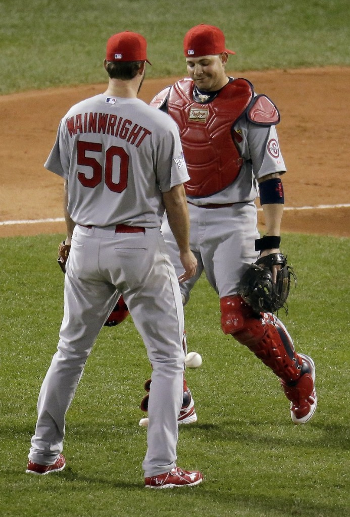 St. Louis Cardinals starting pitcher Adam Wainwright looks at catcher Yadier Molina after neither could catch a pop up by Boston Red Sox's Stephen Drew during the second inning of Game 1 of baseball's World Series Wednesday, Oct. 23, 2013, in Boston. MLB