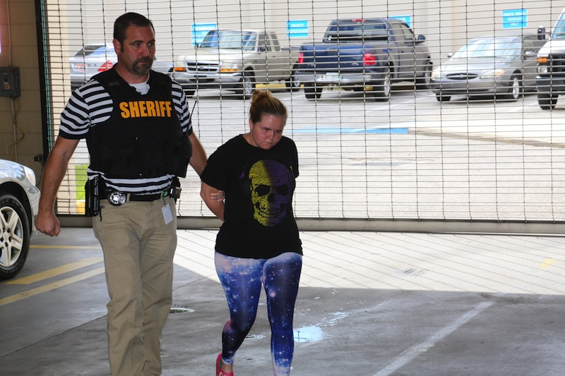 Vivian Vosburg is brought in to the Polk County Jail Booking area by Sheriff Deputy McKinney Friday Oct. 18, 2013, in Bartow Fla. She was arrested at her home in Lakeland Fla. and was to be charged with two counts of Child Abuse with bodily harm and four counts of Child Neglect. Vosburg's charges are not connected to the case involving her daughter, Guadalupe Shaw, of Lakeland, who was charged Tuesday along with Katelyn Roman, 12, with felony aggravated stalking. Guadalupe Shaw and Katelyn Roman are accused of taking part in online and in-person bullying that preceded the suicide of Rebecca Sedwick, 12. She jumped to her death Sept. 10 from the top of an abandoned cement silo in Lakeland.