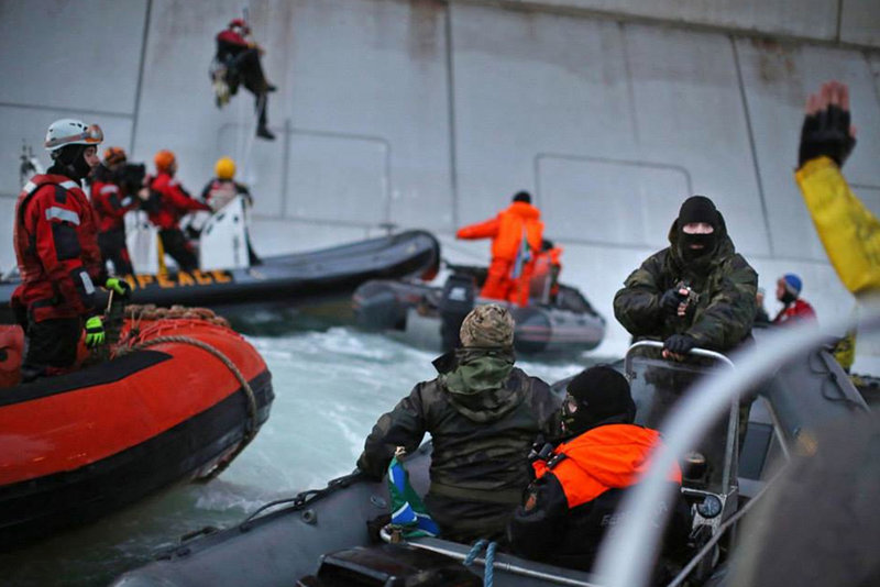 A Russian Coast guard officer is seen pointing a gun at a Greenpeace International activist as five activists attempt to climb the 'Prirazlomnaya,' an oil platform operated by Russian state-owned energy giant Gazprom platform in Russia's Pechora Sea. The activists were there to stop it from becoming the first to produce oil from the ice-filled waters of the Arctic.