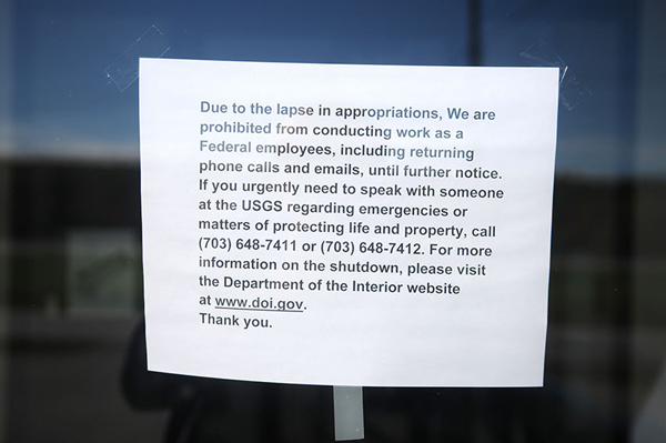 A paper sign describing the government shutdown hangs on the entrance of the U.S. Geological Service building on Whitten Road in Hallowell, Maine.