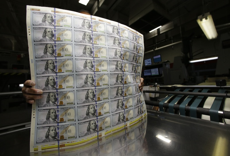This file photo shows sheets of uncut $100 bills moved during the printing process at the Bureau of Engraving and Printing Western Currency Facility in Fort Worth, Texas. The new $100 bill, with a number of high-tech features designed to thwart counterfeiters, will finally get its coming out party on Tuesday, partial government shutdown or not. The Federal Reserve, which has not been affected by the shutdown, will have armored trucks rolling from its regional banks around the country headed to banks, savings and loans and other financial institutions with the new C-notes.