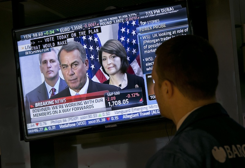 Specialist Frank Masiello watches a television monitor on the floor of the New York Stock Exchange showing a Washington news conference by House Speaker John Boehner, Tuesday, Oct. 15, 2013. Leaders in the House of Representatives and Senate were negotiating separate but similar plans Tuesday to reopen the U.S. government and prevent a default on American debt that economists say could tip the global economy back into recession.
