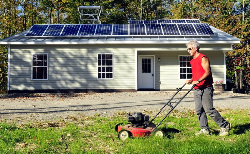 Mike Grant mows the lawn in front of the solar-powered Habitat for Humanity home recently completed on Jacques Lane in Oakland on Thursday. There will be an open house event this Sunday from 1-3 p.m.