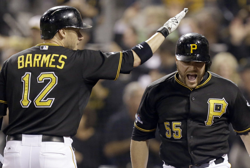 Russell Martin, right, of the Pittsburgh Pirates is welcomed by Clint Barmes after hitting his first of two homers Tuesday night in a 6-2 win against the Cincinnati Reds.
