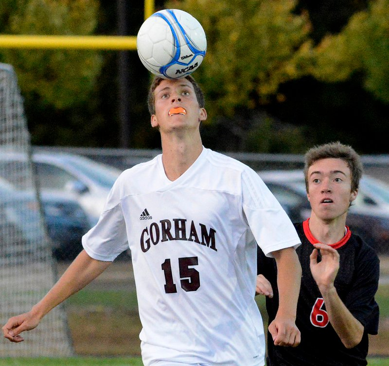 Austin Bell of Gorham holds his ground to head the ball in front of Christian Aguirre of Scarborough during their SMAA boys' soccer game Thursday night. Wyatt Omsberg scored on a penalty kick in overtime to give Scarborough a 2-1 victory.