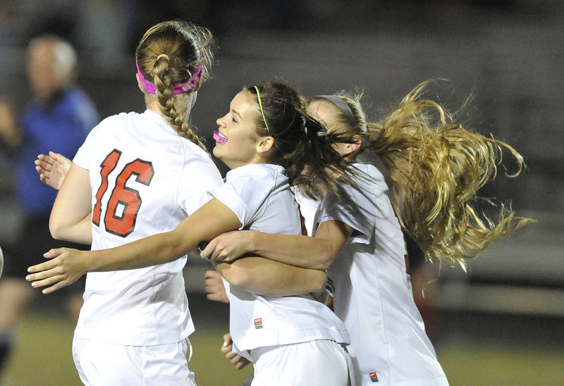 Ashley Perriello, middle, of Scarborough celebrates with Sam Sparda, left, and Morgan Rodway after scoring the only goal in Monday night's win over Gorham.