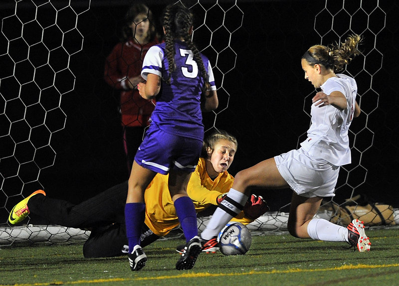 Deering goalkeeper Lee Ann Downs comes out to smother a shot by Hadlee Yescott of Scarborough during undefeated Scarborough's 2-1 victory Wednesday night.