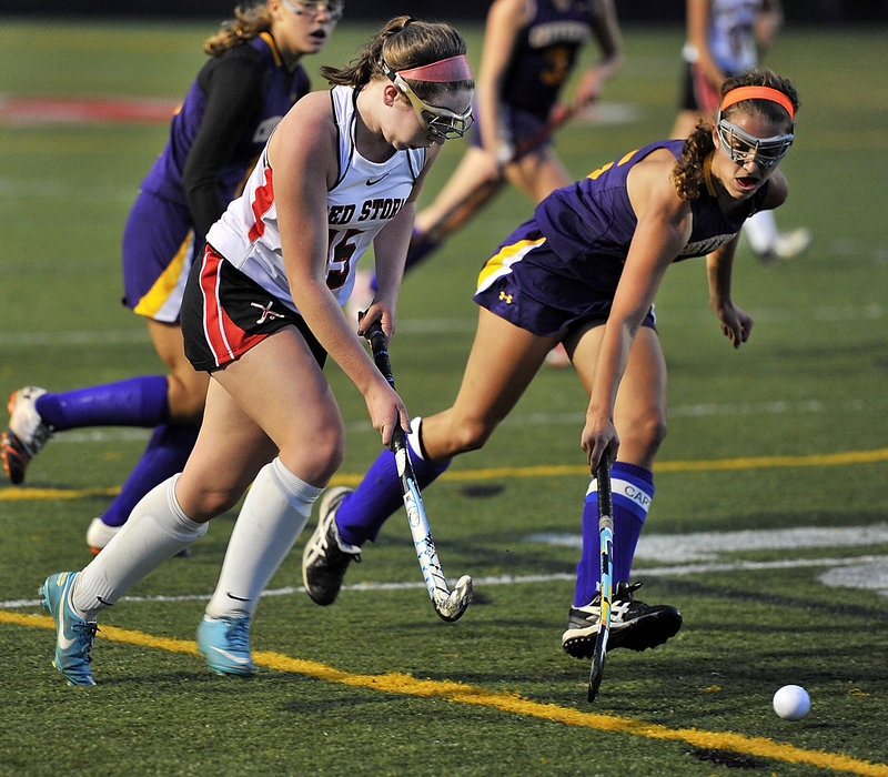 Abby Walker of Scarborough attempts to advance the ball against harassing defense by Elyse Caiazzo of Cheverus.