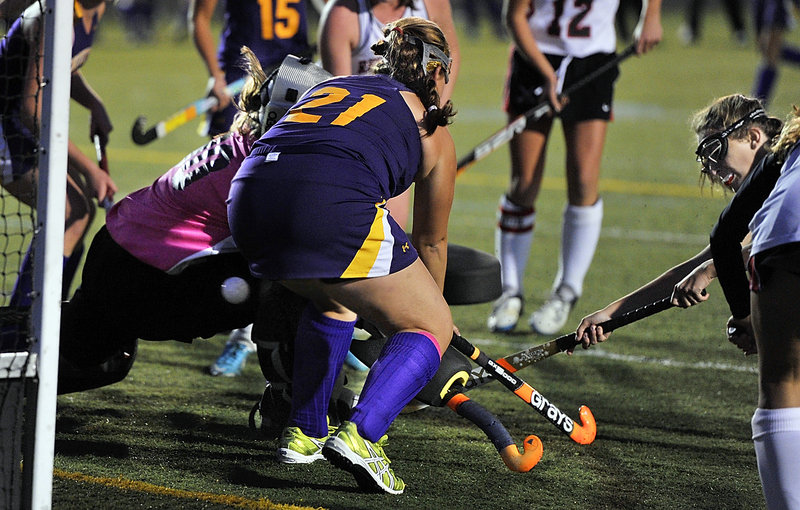 Anna Driscoll of Scarborough pops the ball through defense applied by Sarah Richter of Cheverus and goalie Libby DesRuisseaux to tie the game Thursday night