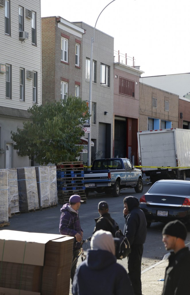 People stand near a row house, center, that was the location of a murder-suicide in the Brooklyn section of New York on Monday. A musician shot and killed two members of an Iranian indie rock band and a third musician early Monday, and wounded a fourth person at their apartment before killing himself on the roof, police and the group's manager said.