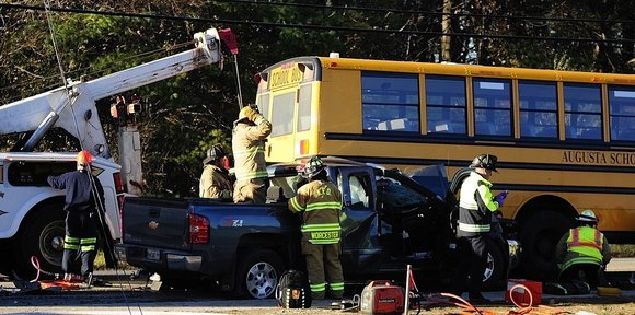 A tow truck lifts a school bus off a pickup truck as emergency crews work to free the pickup truck driver at the scene of a crash involving a school bus Tuesday on Riverside Drive in Augusta.