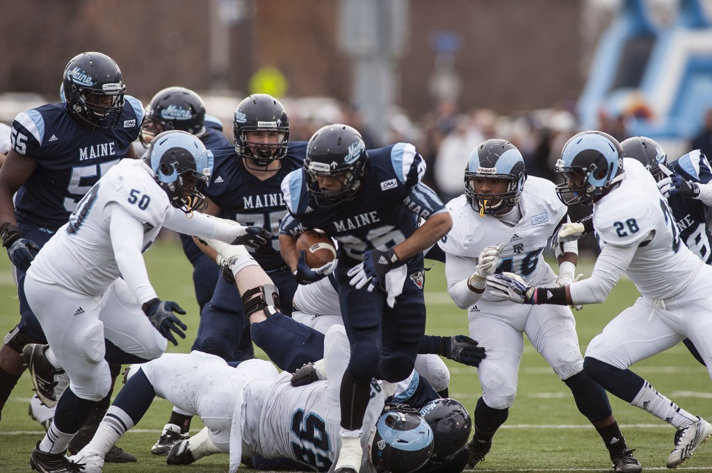 Maine running back Nigel Jones (26) is pursued by Rhode Island defender Shomari Watts, 50, and Adam Parker (46) in the first half of Saturday's game in Orono.