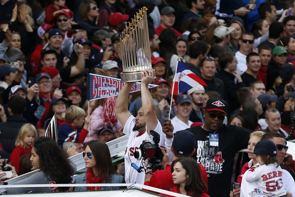Boston's Shane Victorino holds the World Series trophy on Duck Boat during a victory parade celebrating the team's third World Series title since 2004 on Saturday in Boston.