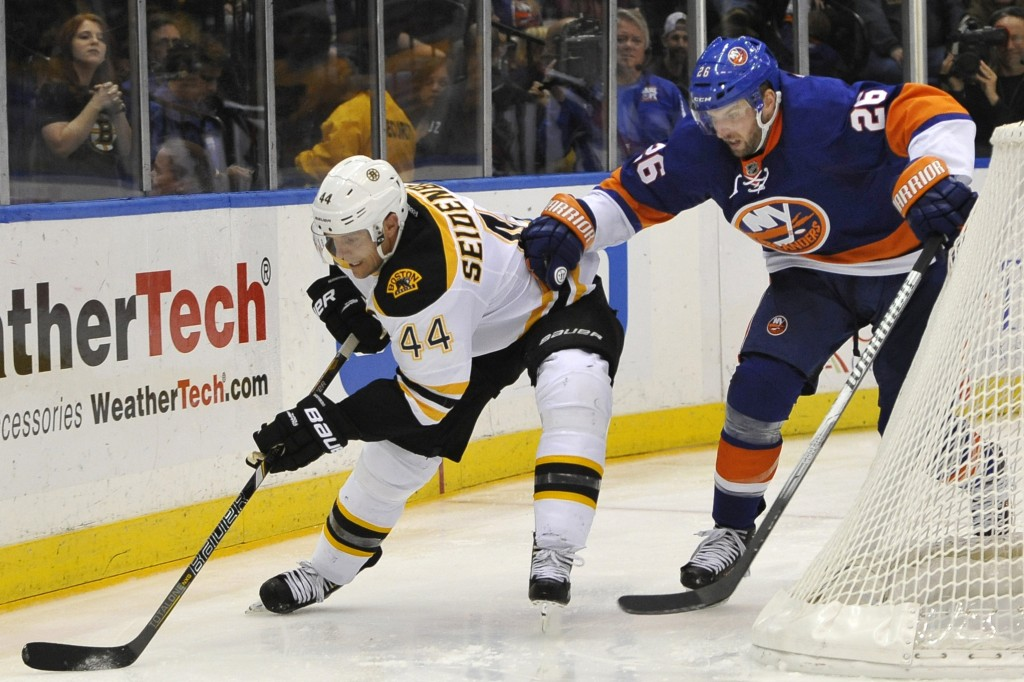New York Islanders' Thomas Vanek chases Boston Bruins' Dennis Seidenberg around the boards in the third period of Saturday night's game on Long Island.