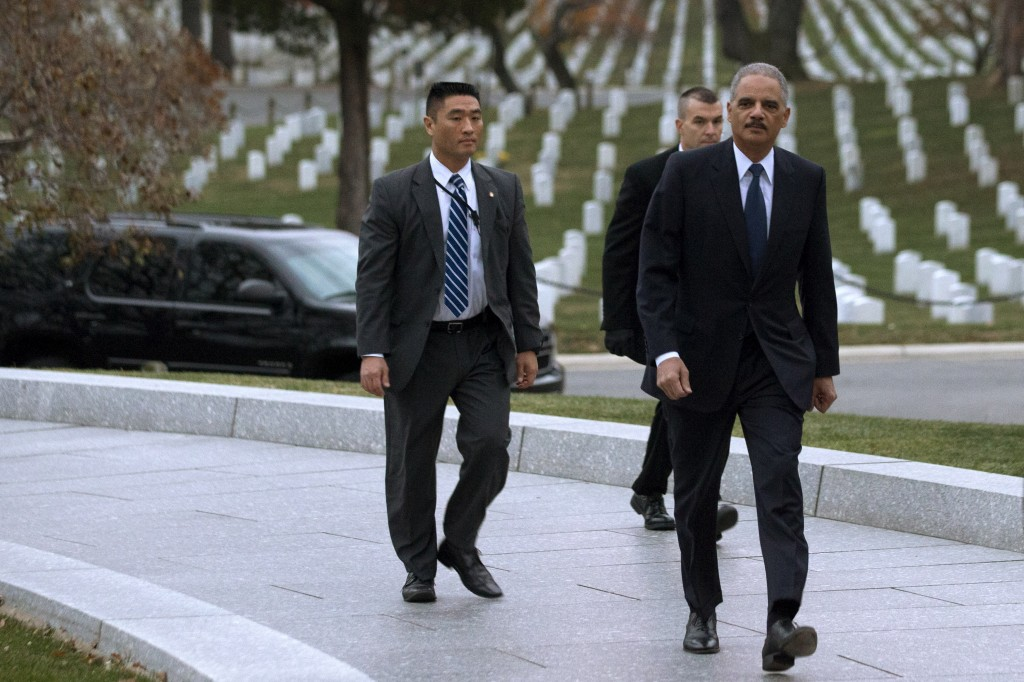 Attorney General Eric Holder, right, arrives to pay his respects at the grave of John F. Kennedy at Arlington National Cemetery on Friday, the 50th anniversary of Kennedy's death. Holder has been visiting the grave since his youth, and would visit there with his mother before she passed away.