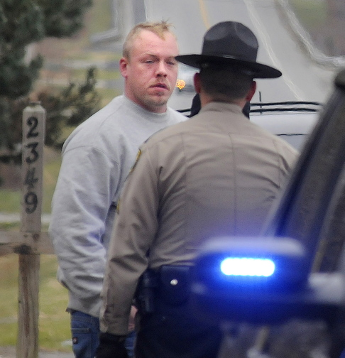 Courtney Shea is interviewed by police on Friday after he reported a body found outside an empty mobile home in Vassalboro. Shea is now charged with murder in Thomas Namer's death.