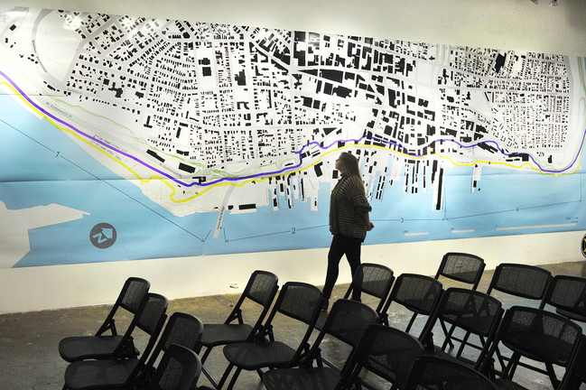 "Orianna Bailey, an intern at Space, studies a large map of Portland that is part of the gallery's exhibition ""Waterfront Visions 2050."""