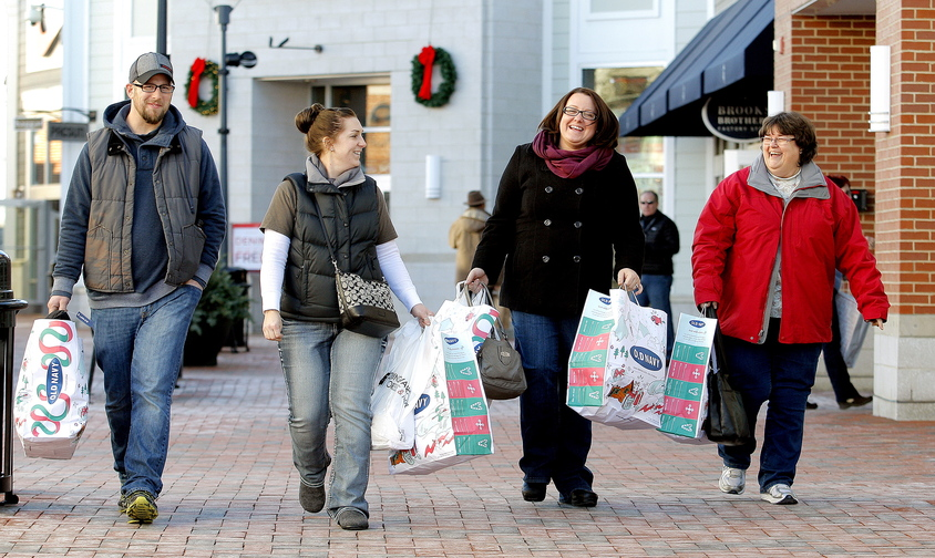 From left, Matt and Amy Powell of Durham, along with Danielle Marston of Norway and mother-in-law Brenda Marston of Oxford, make their way back to their vehicle after shopping at the outlets in Freeport on Friday.