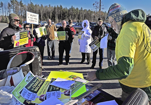 John Newton, right, a member of the executive board of the Maine AFL-CIO, hands out literature Friday to protesters and encourages them to enter the Walmart in Scarborough and talk to employees and customers. Demonstrations were held at about 1,500 Walmarts across the country.