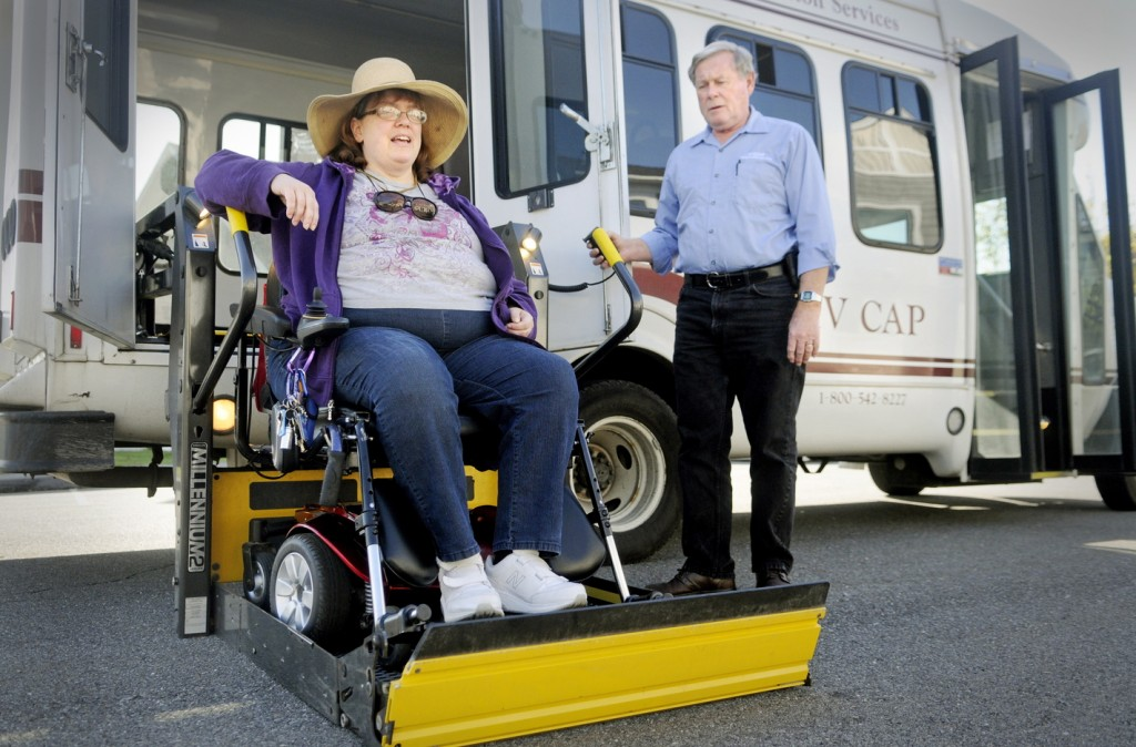 Cynthia Dow is lifted into a bus at her Augusta home Oct. 15 for a ride to an appointment through a MaineCare-sponsored ride service. The revamped transportation system has prompted a flood of complaints about late and missed rides.