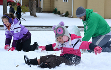 Audree Todd, left, gathers up a snowball to toss at sister Kensie, center, during a snowman-building session with their dad, Casey, at their home in Lawton, Okla., Sunday. The same storm is predicted to move into Maine on Wednesday, but mostly will drop rain instead of snow.
