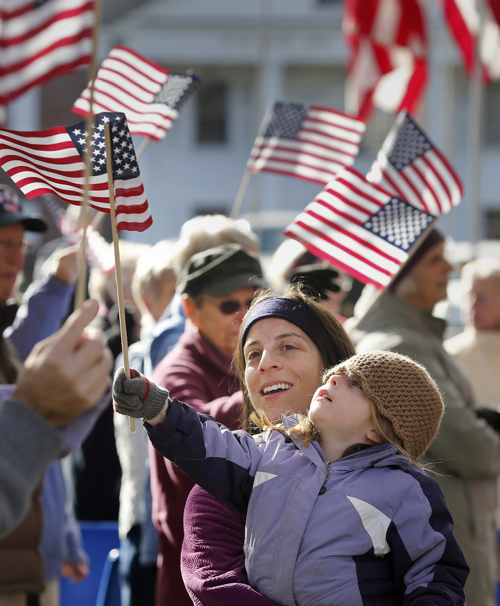 Karin Pires and her daughter Jillian, 4, of Yarmouth greet Korean War veterans Monday as they arrive at Town Hall and Memorial Green in Yarmouth for a Veterans Day ceremony. Korean war veterans traveled in a convoy of buses to locations in Cumberland, North Yarmouth and Yarmouth to be honored in recognition of the 60th anniversary of the Korean armistice agreement.