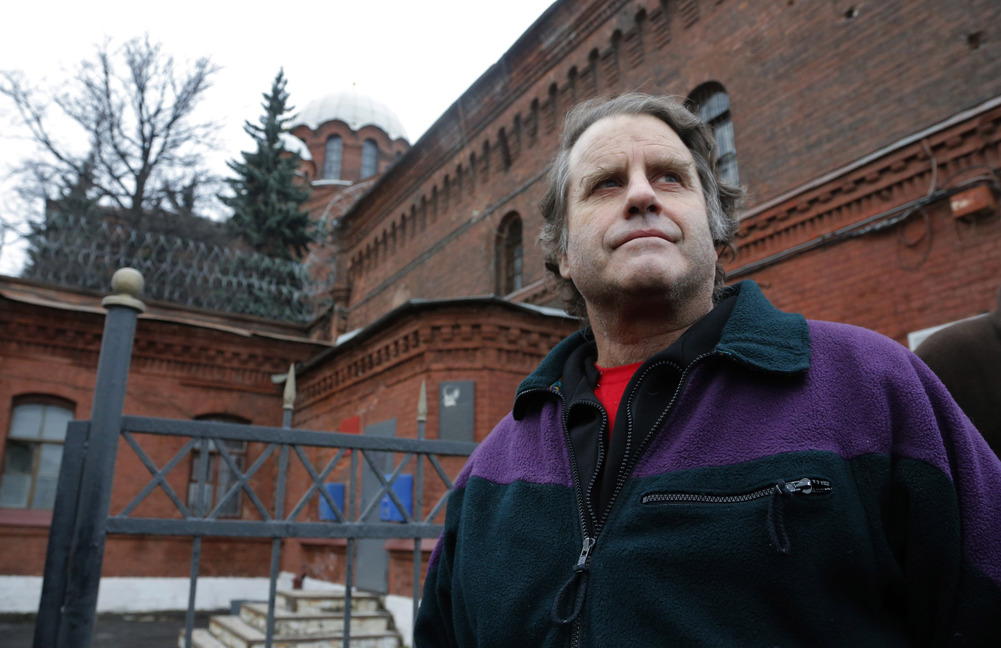 "Greenpeace International activist and the captain of the Greenpeace ship Arctic Sunrise Peter Willcox of the U.S. is released from ""Kresty"" Csosses prison, background, in St.Petersburg, Russia, on Friday. Willxcox is married to an Islesboro woman."