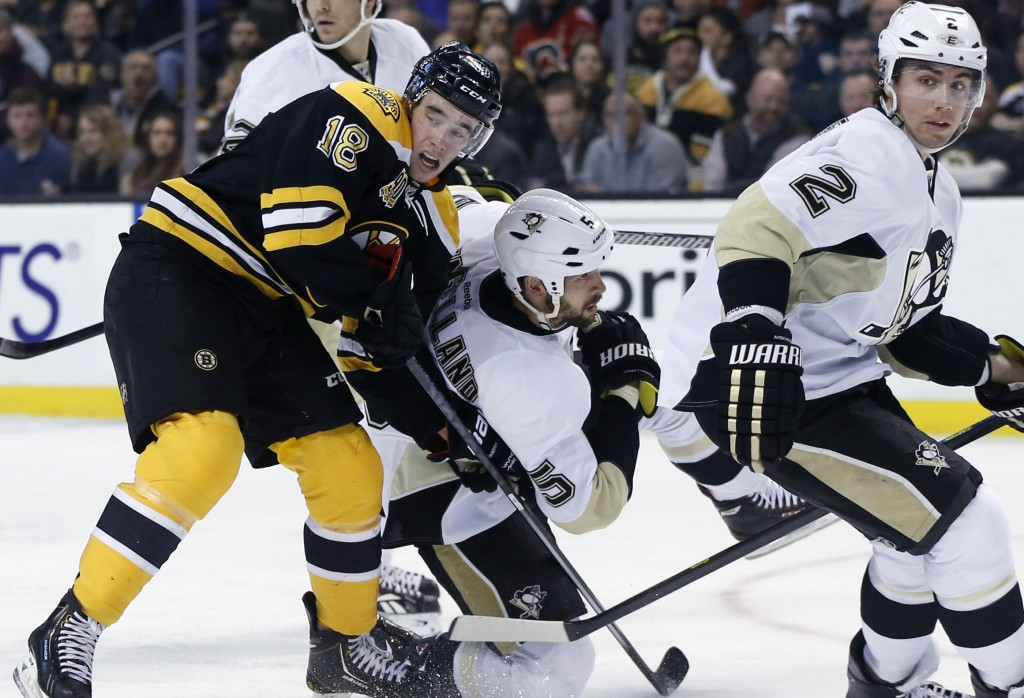 Reilly Smith of the Boston Bruins, left, battles Pittsburgh Penguins defenseman Deryk Engelland, center, as Pittsburgh's Matt Niskanen looks on during Boston's 4-3 overtime win at Boston on Monday night.