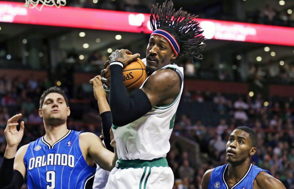 Boston Celtics forward Gerald Wallace, center, grabs a rebound between Orlando Magic center Nikola Vucevic (9) and forward Maurice Harkless, right, during the second half of an NBA basketball game, in Boston, Monday, Nov. 11, 2013.