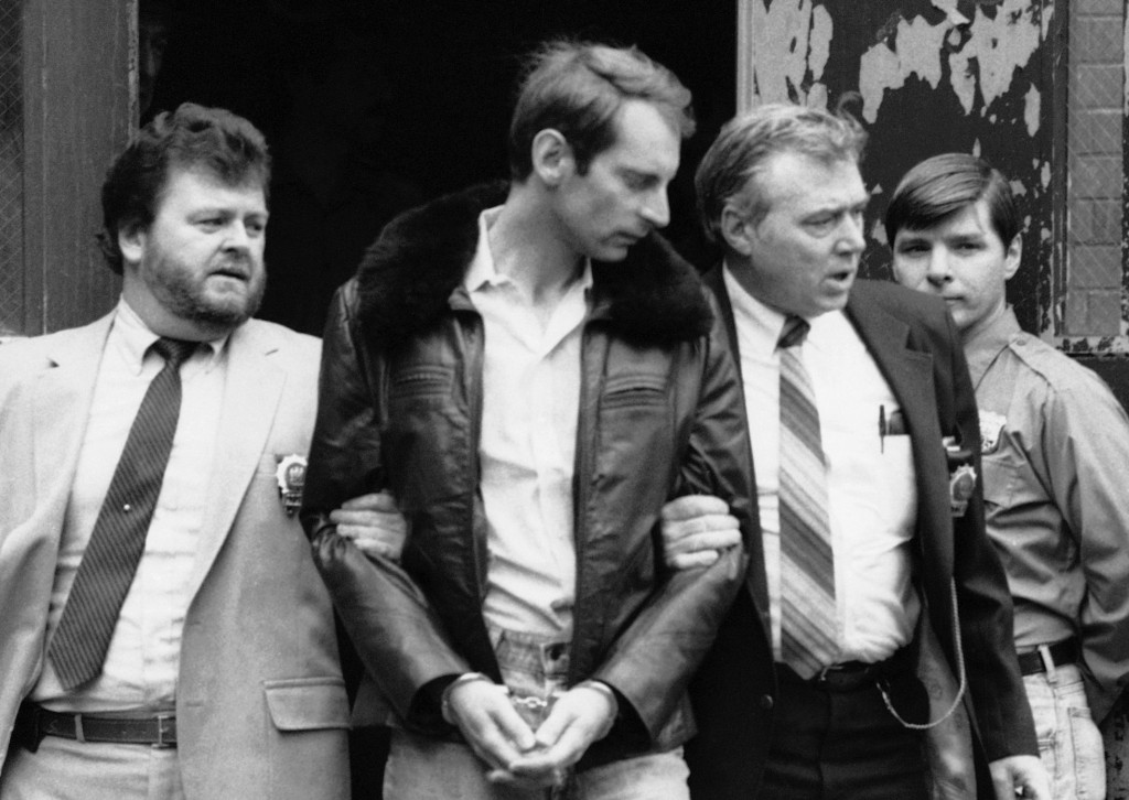 Subway vigilante Bernhard Goetz, second from left, is escorted by police officers as he is taken out of criminal court in New York on Jan. 16, 1985.