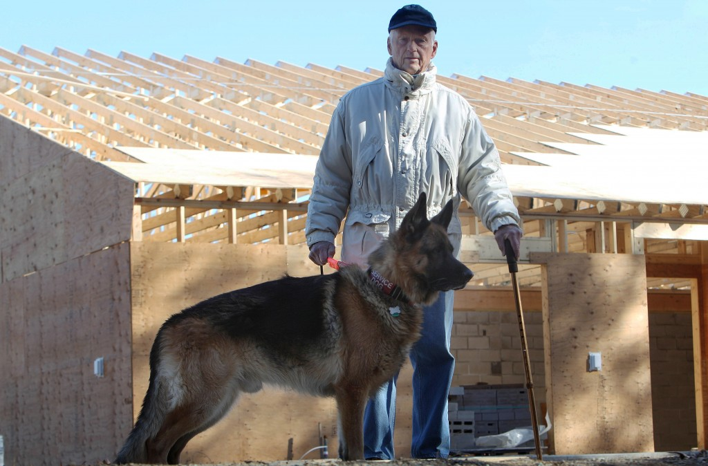Lyman Pope poses with his dog Maximilian outside the construction site of the new SPCA animal shelter in Concord, N.H. Pope, 85, and retired has been spending thousands of dollars in Maine, New Hampshire and Vermont.