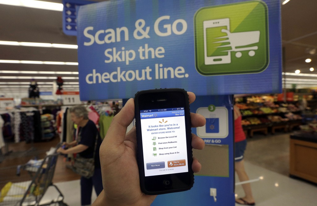 A Wal-Mart representative demonstrates a Scan & Go mobile application on a smartphone at a Wal-Mart store in San Jose, Calif. Wal-Mart is trying to make its mobile app an indispensable tool for customers shopping in its stores. The feature lets customers scan their items as they shop in the aisle and then pay at a self-service register.