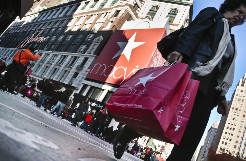 A shopper carries Macy's bags while crossing an intersection outside Macy's on Saturday, Nov. 23, 2013, in New York.